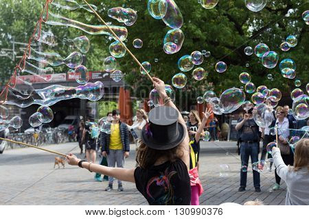 Berlin Germany - may 13 2016: Street artist making soap bubbles on the street in Berlin Germany.