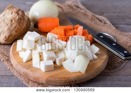 Diced vegetables on a cutting board on a wooden background