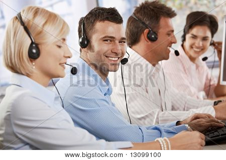 Happy young customer service operator talking via headset, typing on keyboard, looking at camera, smiling.