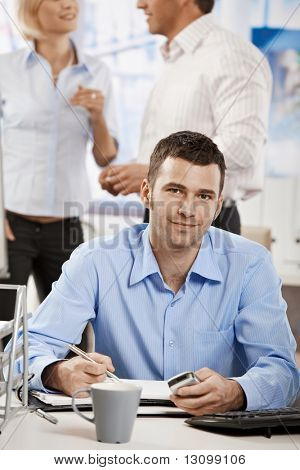 Casual businessman working in office, sitting at desk, writing notes to personal organizer.