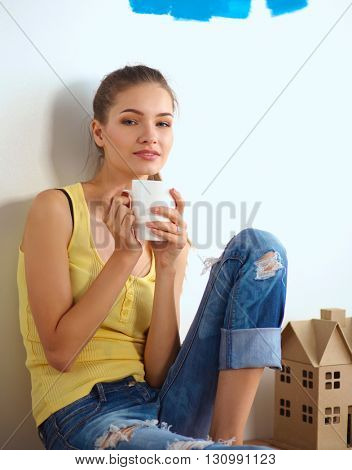 Portrait of female painter sitting on floor near wall after paintingand holding a cup