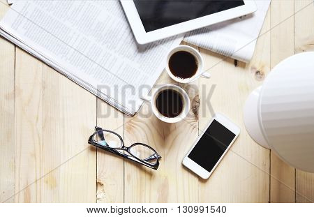 Black coffee with blank digital tablet and mobile phone magazines and glasses on the table. Break concept