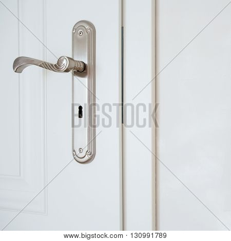 Horizontal view of door-handle in white door