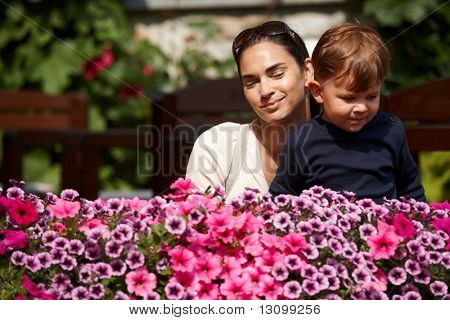 Three years old kid and mother together outdoor in spring garden.
