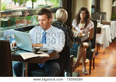 Businessman sitting at table in cafe using laptop computer. Young women having sweets in the background.