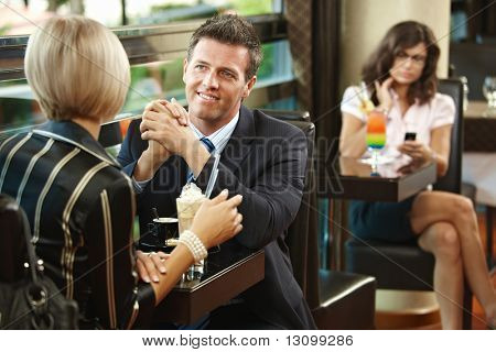 Young businessman and businesswoman having a meeting in cafe.
