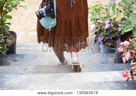 Beautiful female traveler with bandbag and camera on steps in floral garden