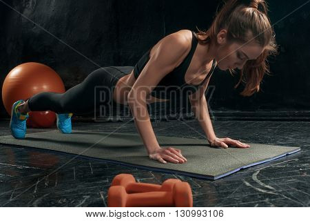 Beautiful young slim woman doing push ups at the gym