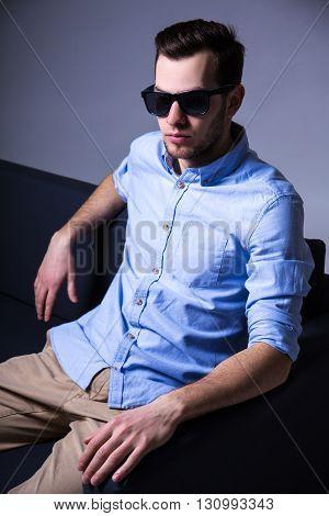 Portrait Of Handsome Man In Sunglasses Sitting On Sofa In Dark Room