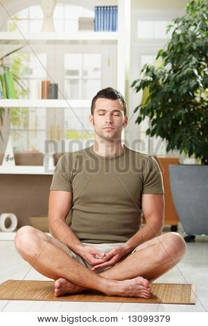 Man doing yoga exercise at home, sitting on floor in living room.