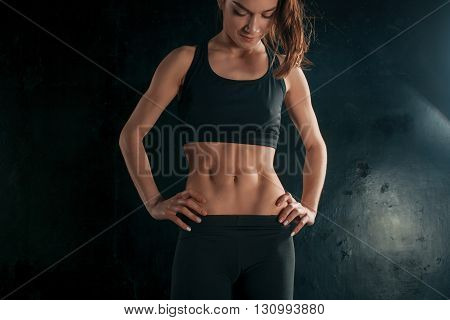 Muscular young woman athlete standing on black background.