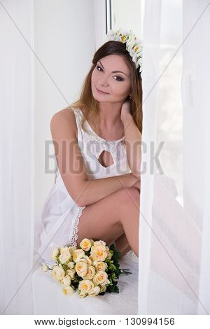 Happy Beautiful Woman In White Dress With Flowers Sitting Near The Window