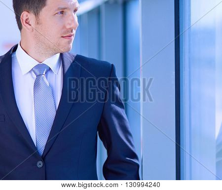 Portrait of businessman standing near window in office