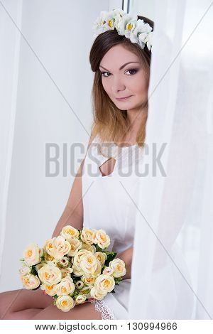 Portrait Of Beautiful Woman In White Dress With Flowers Near The Window