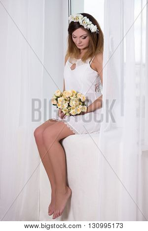 Portrait Of Beautiful Woman In White Dress With Flowers Sitting On Window Sill