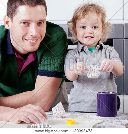 Adorable boy helps his dad bake cupcakes
