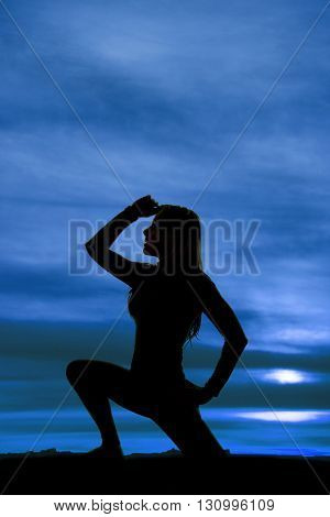 A silhouette of a woman kneeling with her hand up by her head.