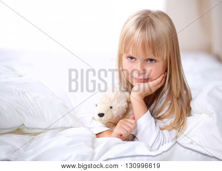 Little girl with teddy bear lying on the bed at home