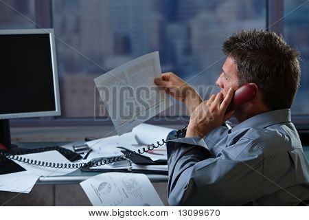 Mid-adult businessman talking on landline phone looking at business documents handheld in closeup.
