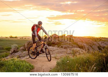 Cyclist Riding the Bike on the Mountain Rocky Trail at Sunset