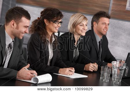 Businesspeople sitting in a row at meeting table in office, looking at somebody out of picture, smiling.
