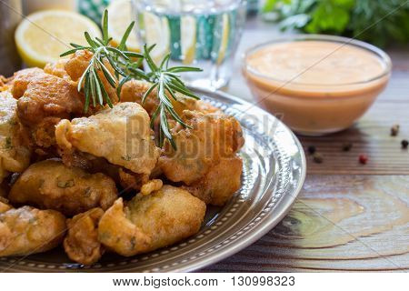 In the foreground shrimps in crispy dough on a plate with rosemary, in the background glass of water, lemon, herbs, bowl with sauce. Shrimps in pastry for lunch. Horizontal. Close.