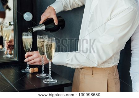 Men Pour Champagne Into Glasses