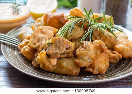 In the foreground shrimps in crispy dough on a plate with rosemary, in the background cutlery, glass of water, lemon, herbs and bowl with the sauce. Shrimps in pastry dressed with sauce. Horizontal.
