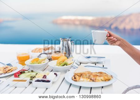 Morning person drinking coffee cup at breakfast table with mediterranean sea view. Woman eating at restaurant outside terrace patio on Santorini, Greece, Europe destination summer vacation.