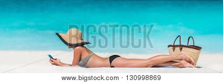 Beach vacation girl using mobile phone app texting sms or browsing on online social media during summer travel holiday. Woman relaxing sunbathing on sand lying on towel wearing sun hat.