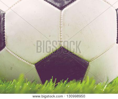 football ball is lying on grass on field