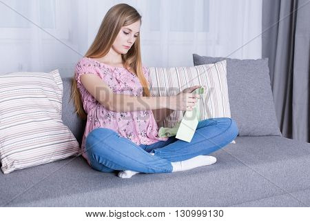 Young and pregnant woman holding baby sleepers