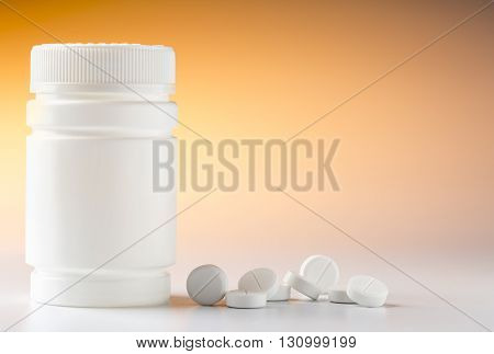 Medicine bottle and various round pills and drugs for pharmacological treatment