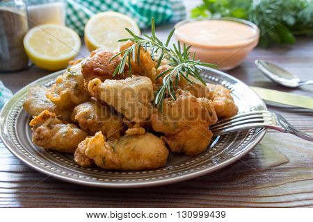 In the foreground shrimps in crispy dough on a plate with rosemary, cutlery, in the background lemon slices, salt, pepper, herbs, bowl with sauce. Shrimps in pastry for lunch. Horizontal. Close.