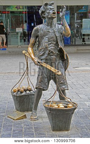 Kunming China - June 8 2015: statue of street seller with two baskets in the center of Kunming China
