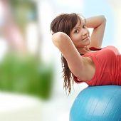 Постер, плакат: Молодой счастливая женщина делает фитнес упражнения дома