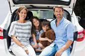 Постер, плакат: Family car trip on summer vacation Happy smiling parents and two children in car having fun Cute s