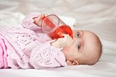 stock photo of babygro  - Feeding procedure of little baby girl on white sheet - JPG