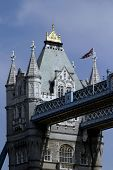 The famous landmark of London: the Tower Bridge. A british flag is flying over it. poster