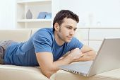 stock photo of belly-band  - Young man laying on sofa and using laptop at home - JPG