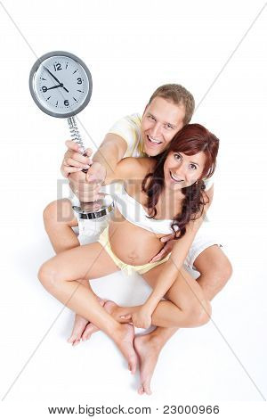 Pregnant Woman With Husband, Holding A Clock Showing 9Th Month, Waiting Anxiously  For The Birth Of