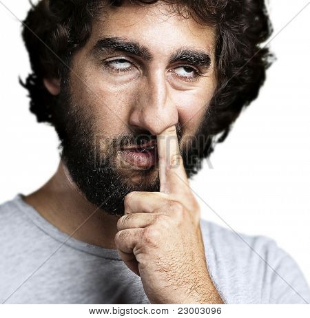 portrait of young man with the finger on his nose against a white background