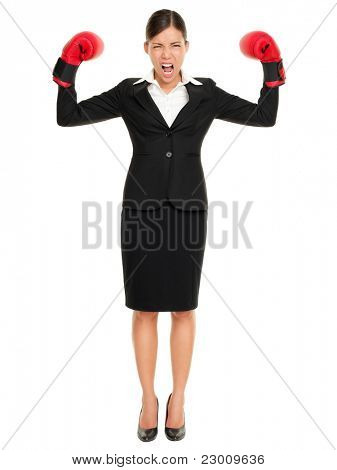 Strong aggressive business woman concept. Businesswoman wearing boxing gloves showing flexing muscles standing in full length wearing suit. Caucasian Asian female model isolated on white background