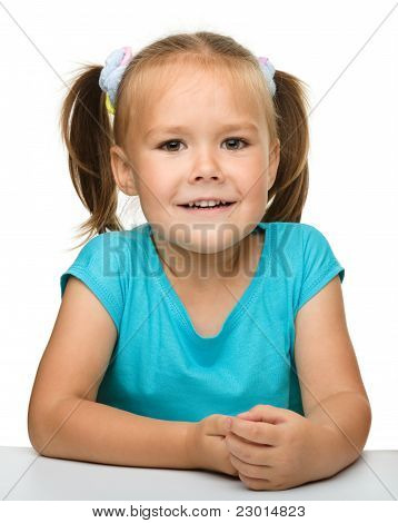 Happy Little Girl Is Sitting At The Table