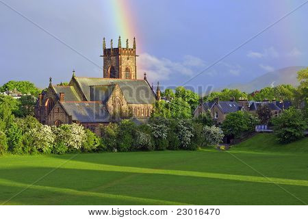 Church with rainbow above it and sun breaking through