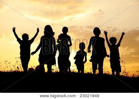 Happy children enjoy on meadow, sunset, summertime