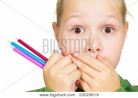 Little Girl Covers Her Mouth With Her Hands And Holding A Pencil In Her Hand Close-up On White Backg