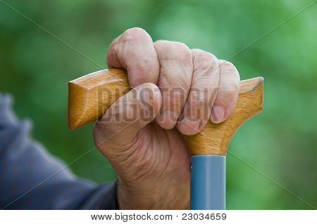 Old tired man's hand holding stick on a green background