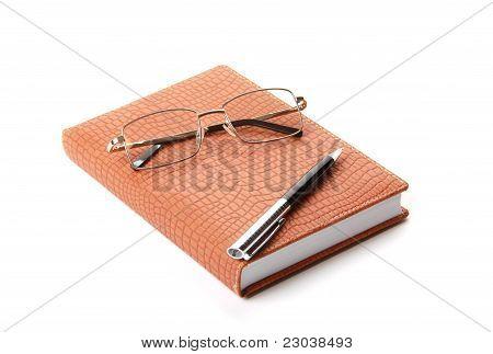 Cuaderno, pluma y anteojos