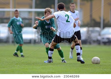 KAPOSVAR, HUNGARY - AUGUST 27: Peter Bokor (white 2) in action at the Hungarian National Championship under 18 game between Kaposvar (green) and Gyor (white) August 27, 2011 in Kaposvar, Hungary.